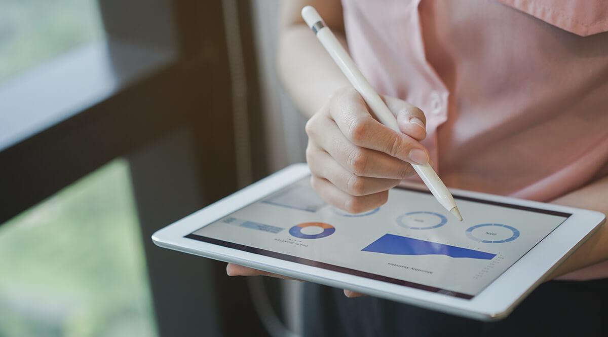 Mulher a consultar num tablet a rentabilidade de ser Parceiro PHC