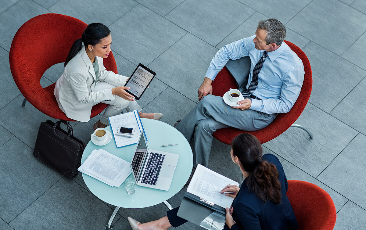 Duas mulheres e um homem em reunião de negócios sobre ser Parceiro PHC